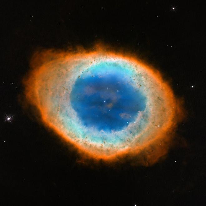 Foto close-up dengan panjang gelombang cahaya tampak oleh teleskop luar angkasa Hubble yang mengungkapkan detail baru dari Nebula Cincin. Kenampakan objek ini tepat mengarah wajah bumi kita sehingga memungkinkan para astronom dapat melihat kenampakan cincin sang nebula. Pengamatan Hubble mengungkapkan bahwa bentuk nebula cincin lebih rumit dari yang selama ini astronom pikirkan. Gas biru dipusat nebula sebenarnya memiliki struktur berbentuk seperti bola yang menembus kemateri seperti donat merah disekelilingnya. Gambar dirilis 23 Mei 2013. Sumber: NASA, ESA, (STScI/AURA)-ESA/Kolaborasi Hubble.