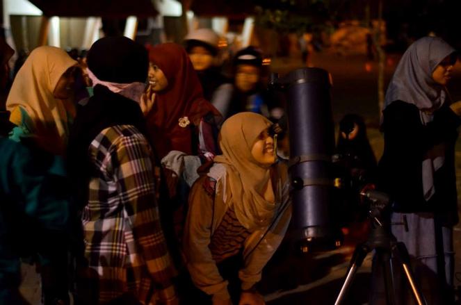 Salah satu pengunjung menikmati keindahan permukaan bulan dari balik lensa. Sumber : Hariyanto Surbakti